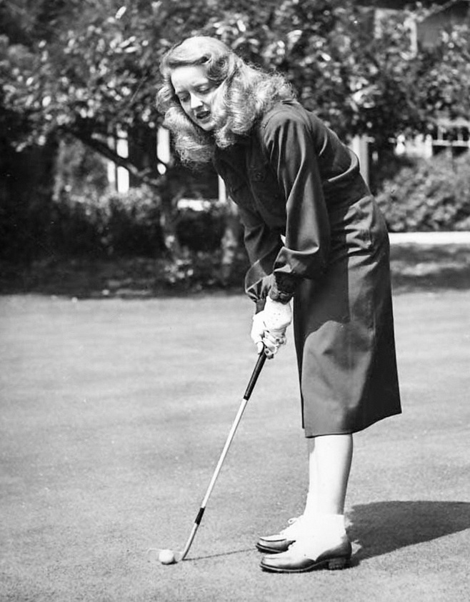 Bette Davis playing golf in sensible shoes, 1930s