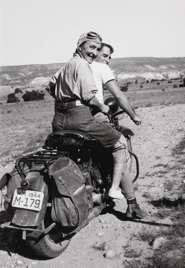 Artist Georgia O'Keefe riding on the back of a motorcycle, New Mexico, 1940s