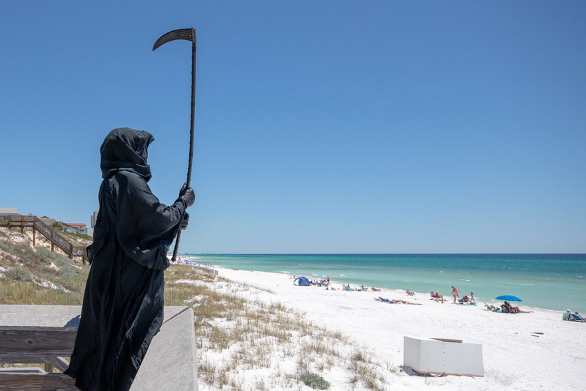 Person dressed up as the Grim Reaper gently reminding people going to the beach in Florida that there is still a pandemic going on