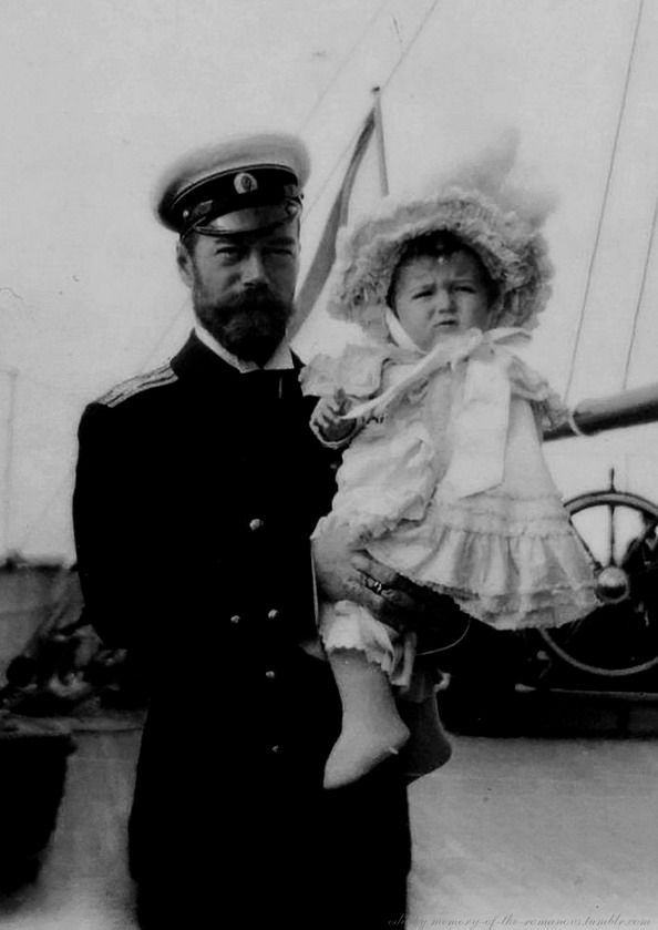 Nicholas II with his young son in a dress and frilly bonnet