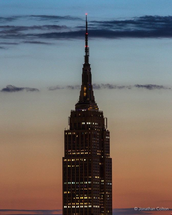 The top of the Empire State Building (NYC) on a recent evening, gone dark in order to pay tribute to victims of one or another unfolding national tragedies in the US
