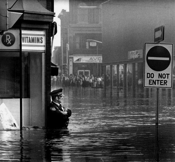 Policeman standing guard during a flood in Ontario,1970s