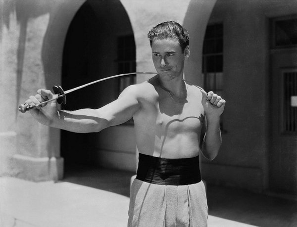 Shirtless Errol Flynn about to whip you with his epée