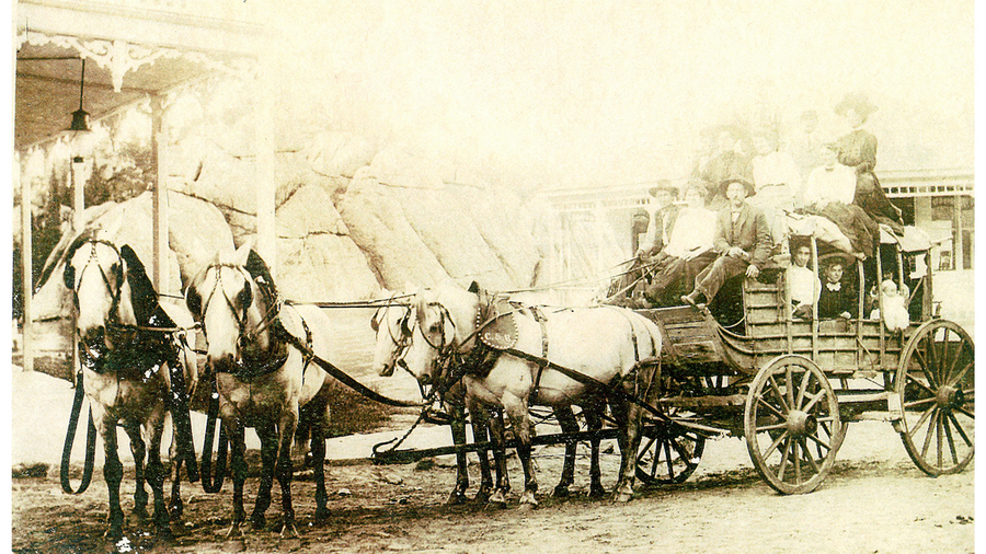 A team of four white horses pulling a stagecoach, 1800s
