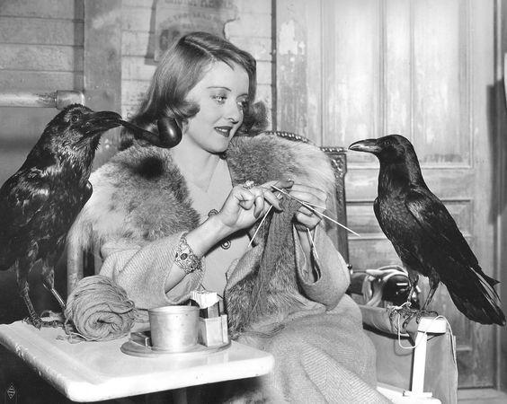 Bette Davis knitting while two ravens lookon