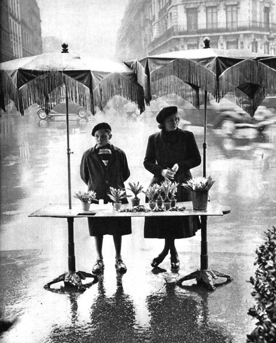 Selling flowers in the rain, Place Victor-Basch, Paris, circa 1950. Photograph by Izis Bidermanas.