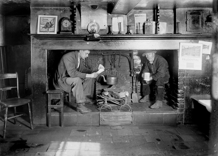 Two men warming up inside a fireplace, before central heating became a thing in England