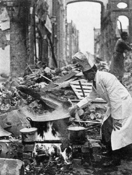Chef preparing food in the rubble of Bristol, England, after a Nazi bombing raid inWWII
