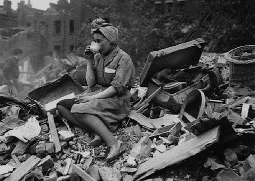 Woman having a tea break on top a pile of rubble after a Nazi bombing run on London, WWII
