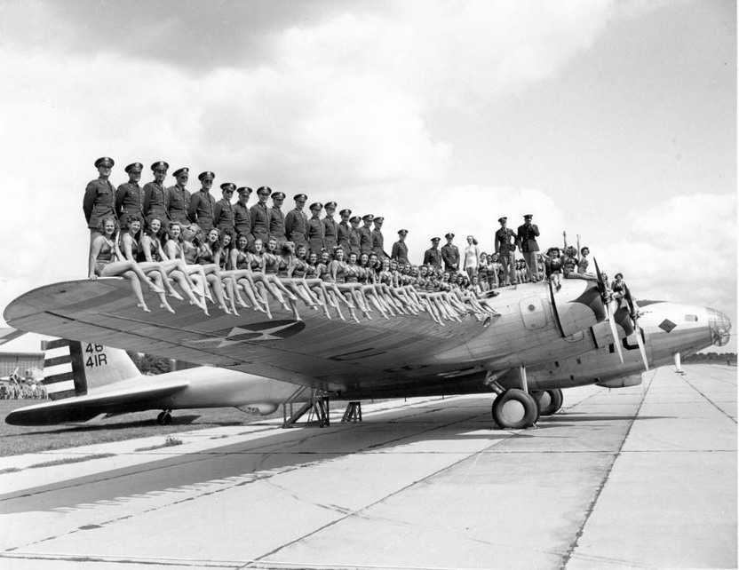 The Rockettes pose with service members on the wing of an American bomber, WWII