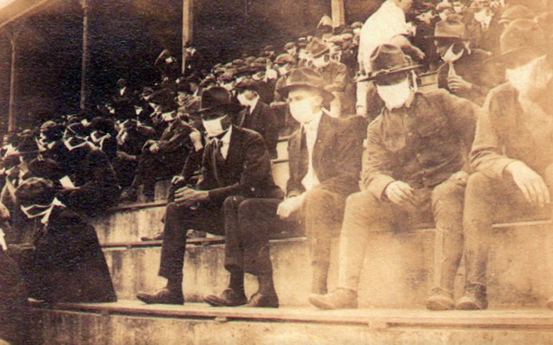 Spectators at a sports game or races wearing masks during the 1918-19 Pandemic