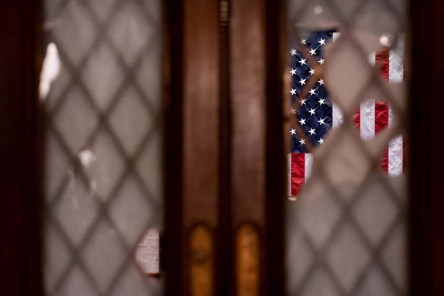 American flag seen through shattered windows in the US Capitol after the attempted coup by the Republicans