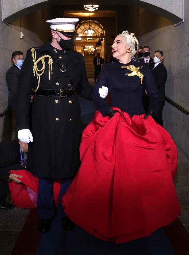 Lady Gaga being escorted to perform at the Bideninauguration