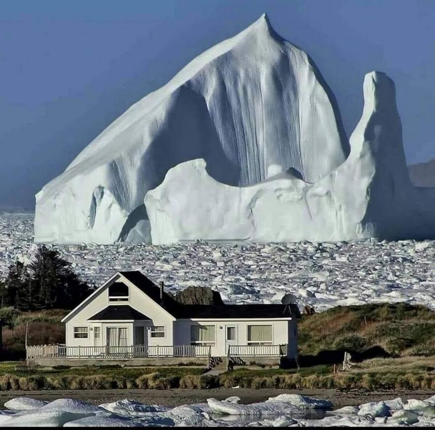 Giant iceberg floating in the Atlantic Ocean near a house in Newfoundland,Canada