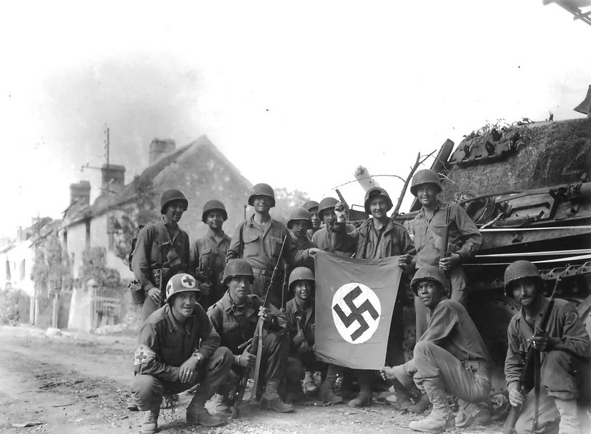 American troops holding a captured Nazi flag as they invade Germany,1945