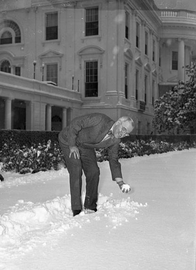 President Harry Truman making a snowball outside the White House, 1940s