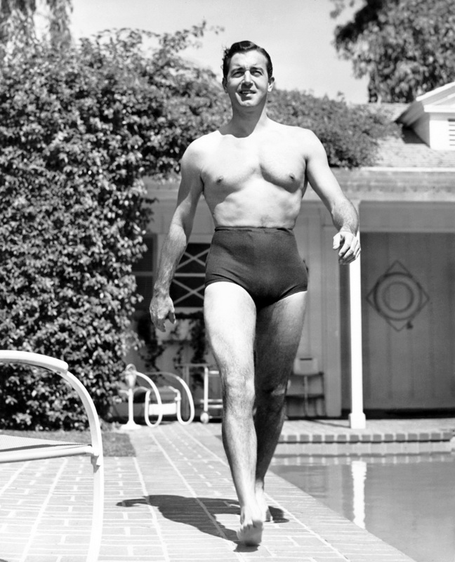 Actor John Payne strutting in a pair of hi-rise swim shorts, 1940s
