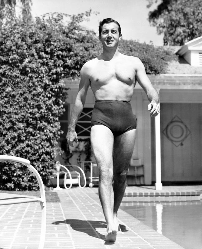 Actor John Payne strutting in a pair of hi-rise swim shorts,1940s
