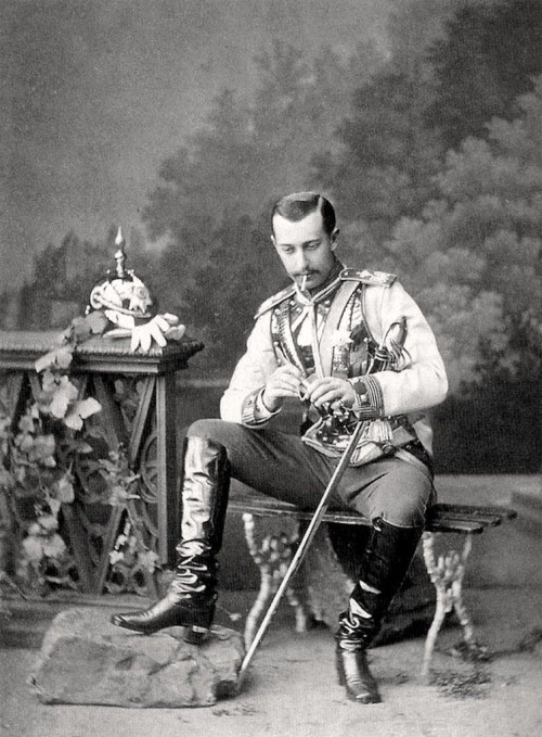 PRINCE SERGEI MAXIMILIANOVICH ROMANOVSKY OF LEUCHTENBERG DE BEAUHARNAIS, putting down his pickelhaube, lighting a smoke, and showing off his shiny boots