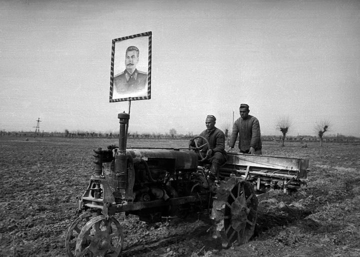 Tractor with a portrait of Stalin overseeing the work of collectivized farmers, SovietUnion