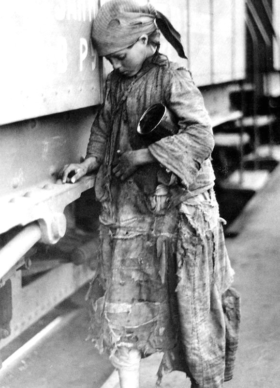 Girl trying to pick up single bits of wheat from a train during the 1930s famine Stalin caused by idiotic agriculturepolicies