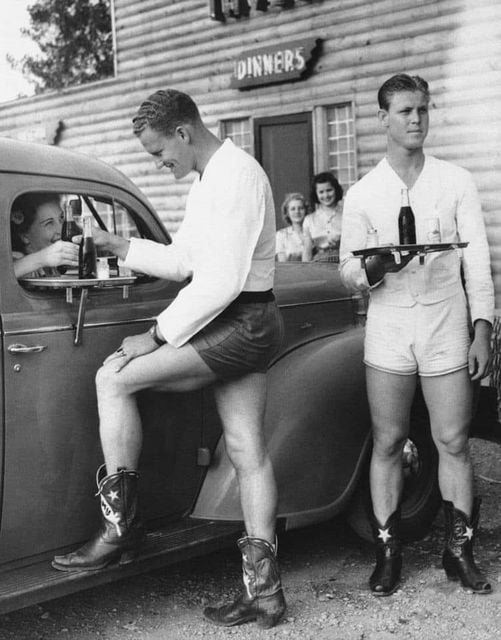 Waiters in hot pants and cowboy boots serving up customers at a roadside diner, Dallas, Texas, 1940s