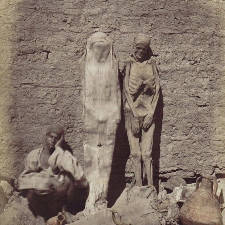 Egyptian man selling mummies on the street,1800s