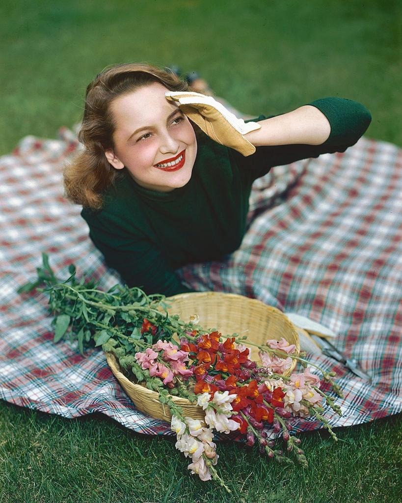 Olivia DeHaviland with some snapdragons,1940s