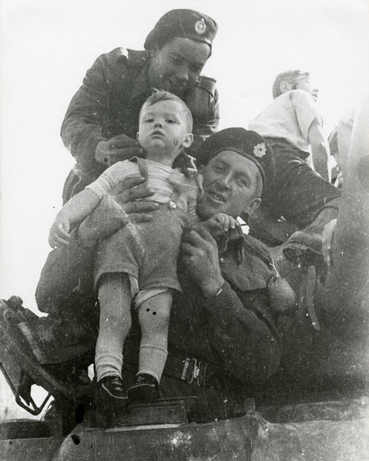 Canadian soldiers with a Dutch child during the liberation of the Netherlands from the Nazis,WWII