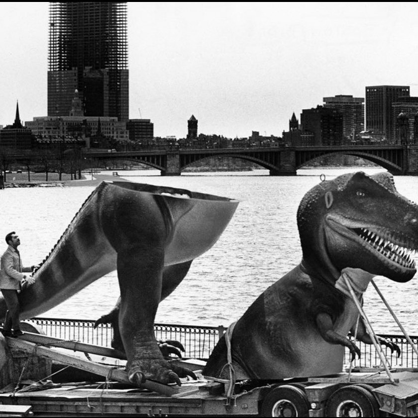 Boston under construction: John Hancock Tower being built while new, giant dinosaur replica is being delivered to the Museum of Science,1972
